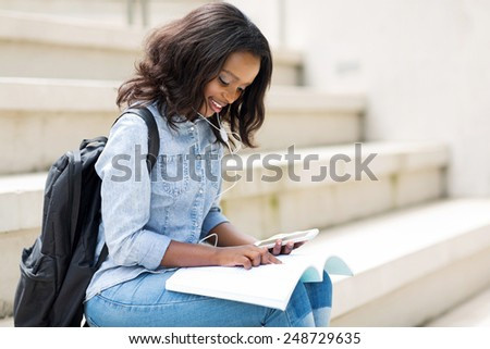 pretty young afro american college girl reading on campus #248729635