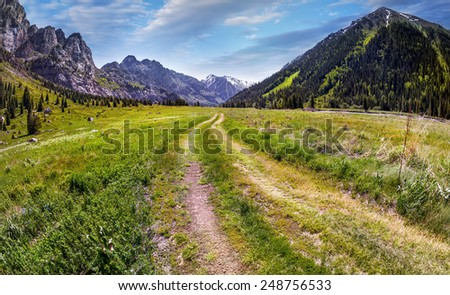 Road in Mountain valley at blue sky in Dzungarian Alatau, Kazakhstan, Central Asia #248756533