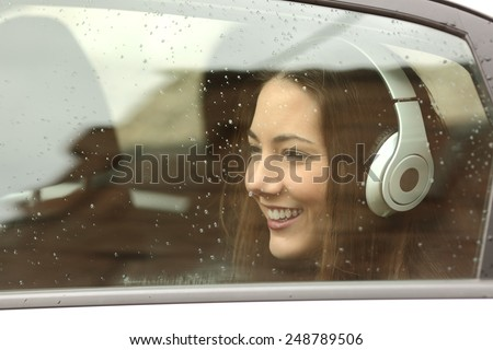 Happy teenager with headphones listening to the music inside a car and looking away #248789506
