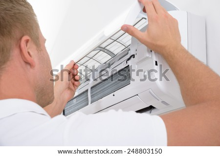 Portrait Of A Young Man Adjusting Air Conditioning System #248803150