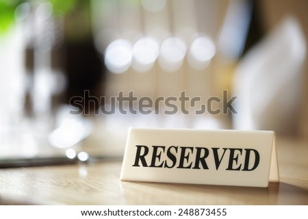 Restaurant reserved table sign with places setting and wine glasses Royalty-Free Stock Photo #248873455
