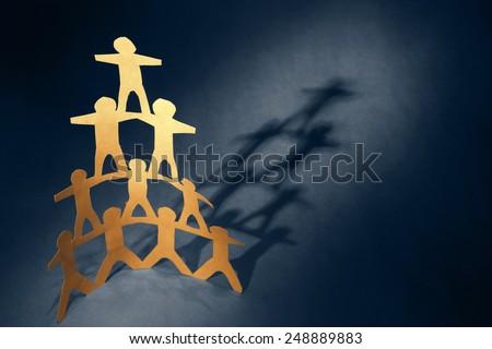 Human team pyramid holding hands Royalty-Free Stock Photo #248889883