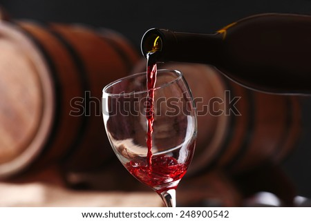 Pouring red wine from bottle into glass with wooden wine casks on background #248900542