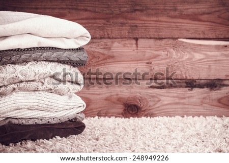 stack of sweaters on a wooden background. vintage toning #248949226