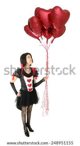 A pretty young teen in a Valentine dress looking up at the fistful of heart-shaped balloons she  holds.  On a white background.  #248951155
