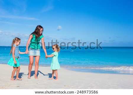 Young happy mother and little girl having fun during beach vacation #248973586