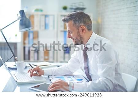 Elegant businessman analyzing data in office Royalty-Free Stock Photo #249011923