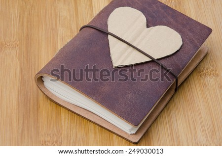 closeup of an old notebook with a cardboard heart on top on a wooden table