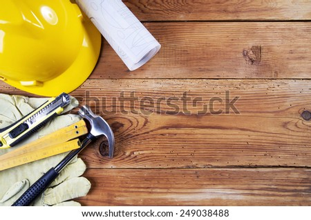hammer, protective gloves, folding ruler, model knife, blueprint and yellow safety helmet on wooden background #249038488