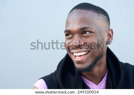Close up portrait of a cheerful young african american man smiling against gray background  #249100054