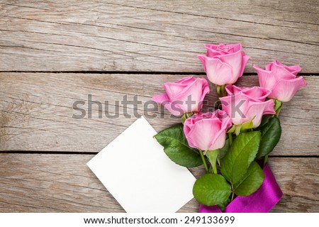 Pink roses and valentines day blank greeting card or photo frame over wooden table. Top view with copy space