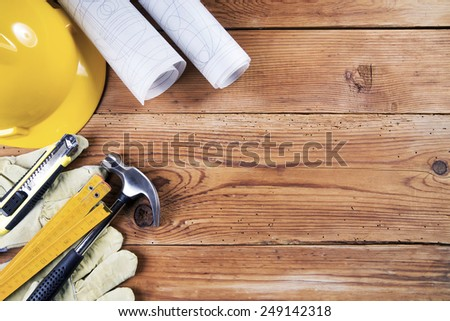 hammer, protective gloves, folding ruler, model knife, blueprint and yellow safety helmet on wooden background #249142318