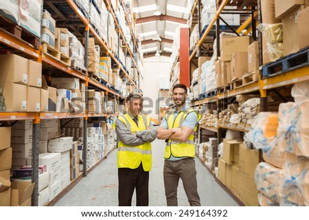 Warehouse team standing with arms crossed in a large warehouse #249164392