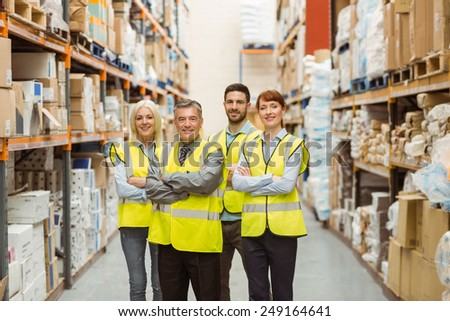 Smiling warehouse team with arms crossed in a large warehouse #249164641