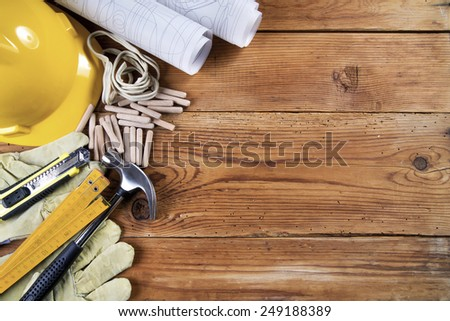 hammer, protective gloves, folding ruler, model knife, blueprint,  wooden dowels, electrical cable  and yellow safety helmet on wooden background #249188389