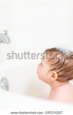 Cute baby girl taking a bath with bubbles. #249214207