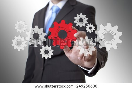 Businessman playing with gears and various cogwheels #249250600