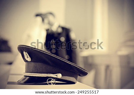 wedding photo with rings and police or military officer hat