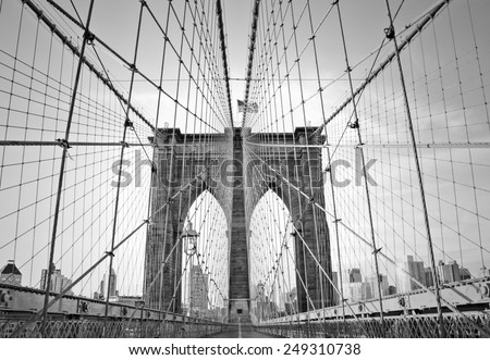 A black and white photo from inside the wires of the Brooklyn Bridge, looking on to New York City.