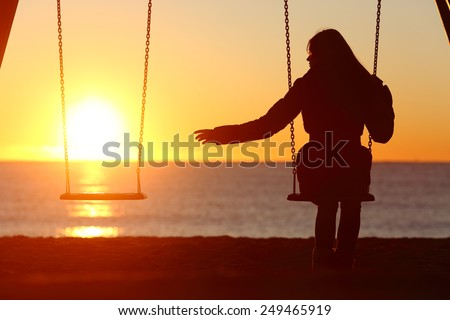 Single or divorced woman alone missing a boyfriend while swinging on the beach at sunset #249465919