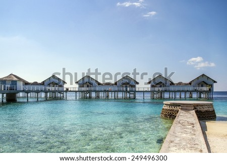 Picturesque bungalows on stilts near the shore of a tropical island, Maldives #249496300