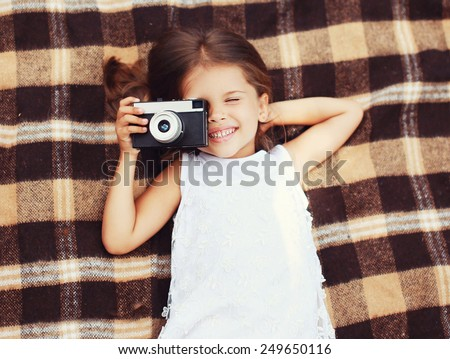 Funny child shooting vintage old retro camera and having fun on the plaid, top view