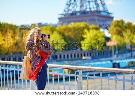 Young tourist in Paris taking picture of the Eiffel tower