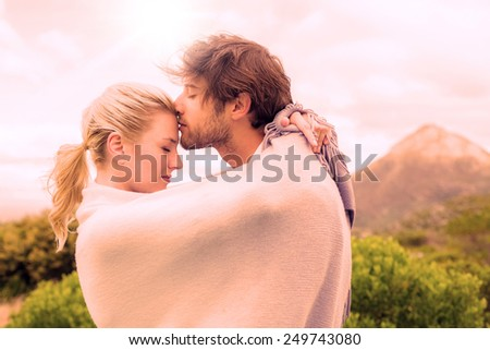 Cute affectionate couple standing outside wrapped in blanket on a chilly day #249743080