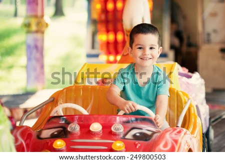 Happy smilling boy driving car toy at an amusement park. Toned photo. Royalty-Free Stock Photo #249800503