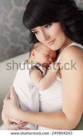 portrait of Young happy mother with her newborn baby lying on bed in home interior. happy mother holding her baby and playing with him indoors. Mother and baby #249804265