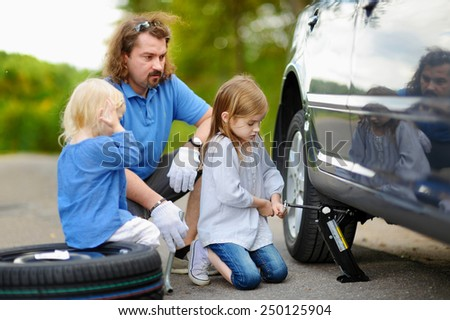 Adorable little girl helping her father to change a car wheel outdoors on beautiful summer day #250125904