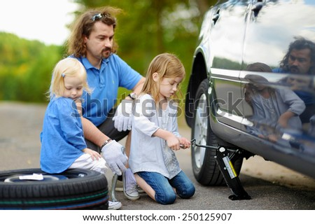 Adorable little girl helping her father to change a car wheel outdoors on beautiful summer day #250125907