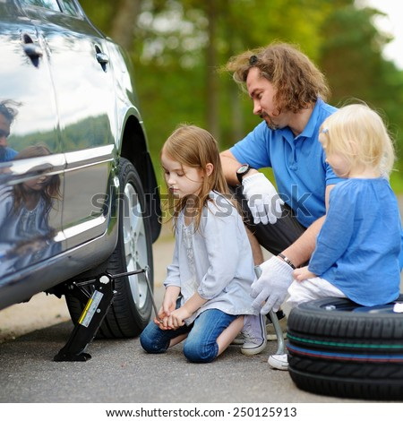 Adorable little girl helping her father to change a car wheel outdoors on beautiful summer day #250125913