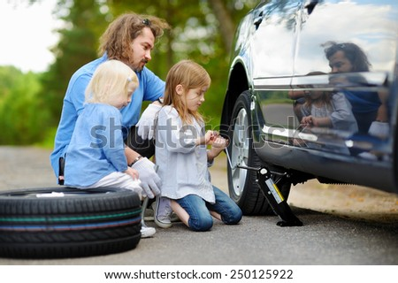 Adorable little girl helping her father to change a car wheel outdoors on beautiful summer day #250125922