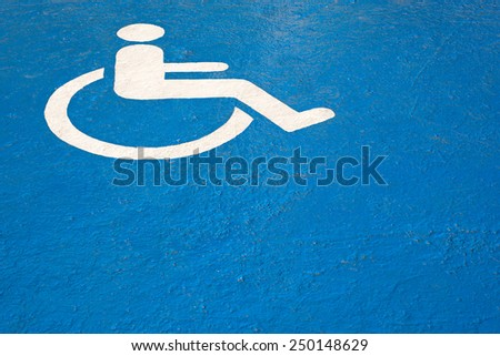 Blue rectangle handicapped sign with wheelchair a cement floor. #250148629