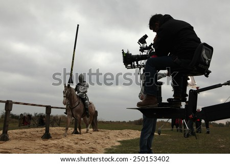 MILOVICE, CZECH REPUBLIC - OCTOBER 23, 2013: Actor dressed as a medieval knight rides a horse during the filming of the new movie The Knights near Milovice, Czech Republic. #250153402