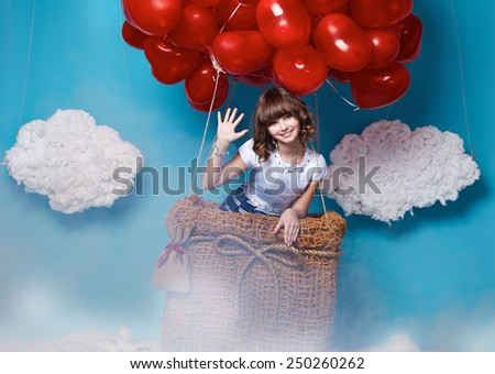 Small cute girl with beautiful face on a board with a lot of red balloons having heart form on  top flying in happy mood under bright blue sky with clouds and wind playing with her hair Valentines day