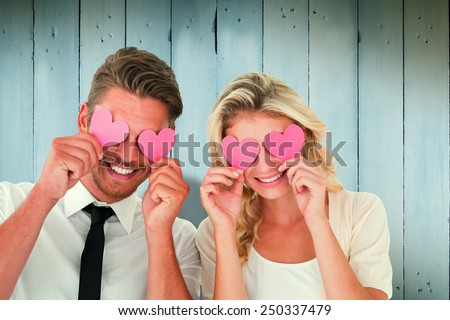 Attractive young couple holding pink hearts over eyes against wooden planks #250337479