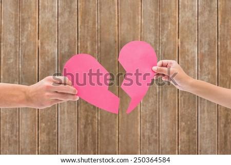 Hands holding two halves of broken heart against wooden planks #250364584