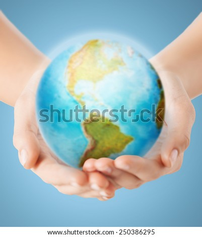 people, geography, population and peace concept - close up of human hands with earth globe showing american continent over blue background #250386295