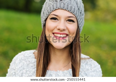 Close up portrait of young woman smiling in a park.  #250555441