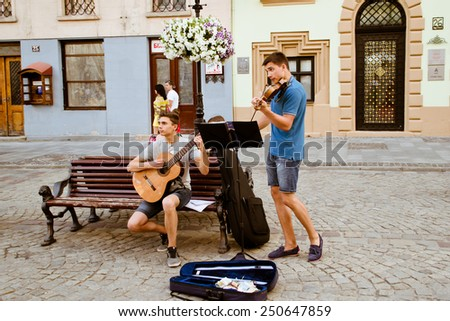LVIV, UKRAINE - JULY 22: Street musicians on a central square of the city in the Ukraine on July 22, 2014 in Lviv. #250647859
