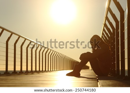 Sad teenager girl depressed sitting in the floor of a bridge on the beach at sunset #250744180