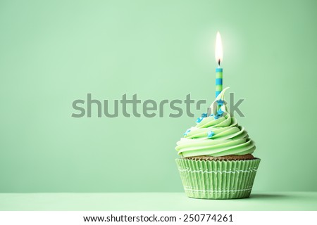 Green birthday cupcake with copy space to side Royalty-Free Stock Photo #250774261
