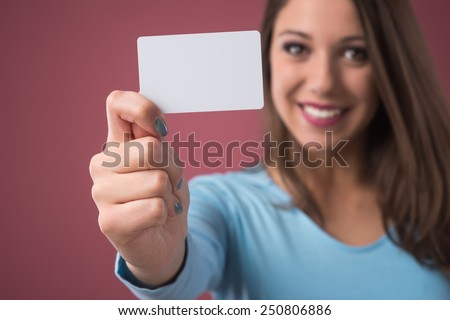 Smiling young woman holding a blank business card and looking at camera
