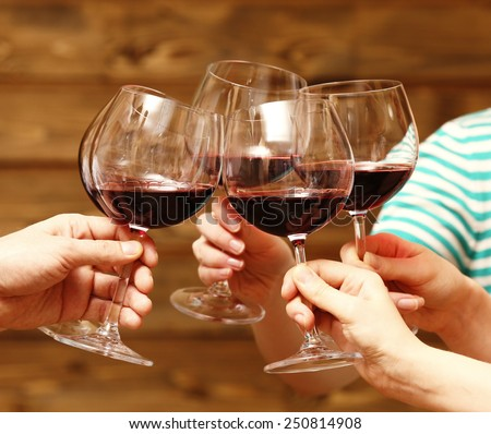 Clinking glasses of red wine in hands on rustic wooden planks background #250814908