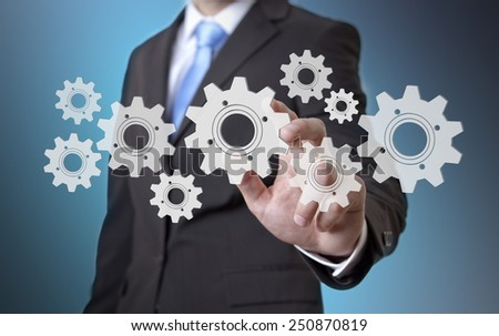 Businessman playing with gears and various cogwheels #250870819