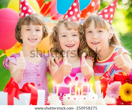 Group of happy children celebrating birthday. Kids having fun in spring garden #250958275