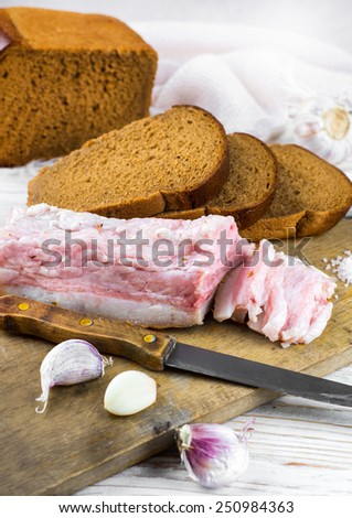 Bacon with onion and garlic on a wooden board #250984363