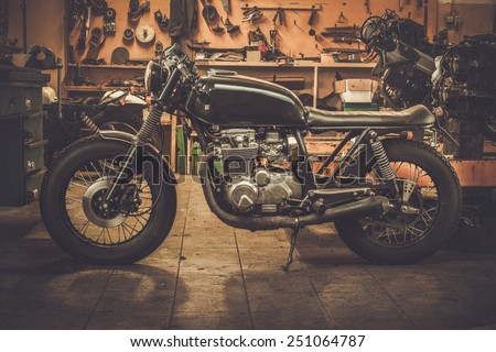 Vintage style cafe-racer motorcycle in customs garage  Royalty-Free Stock Photo #251064787